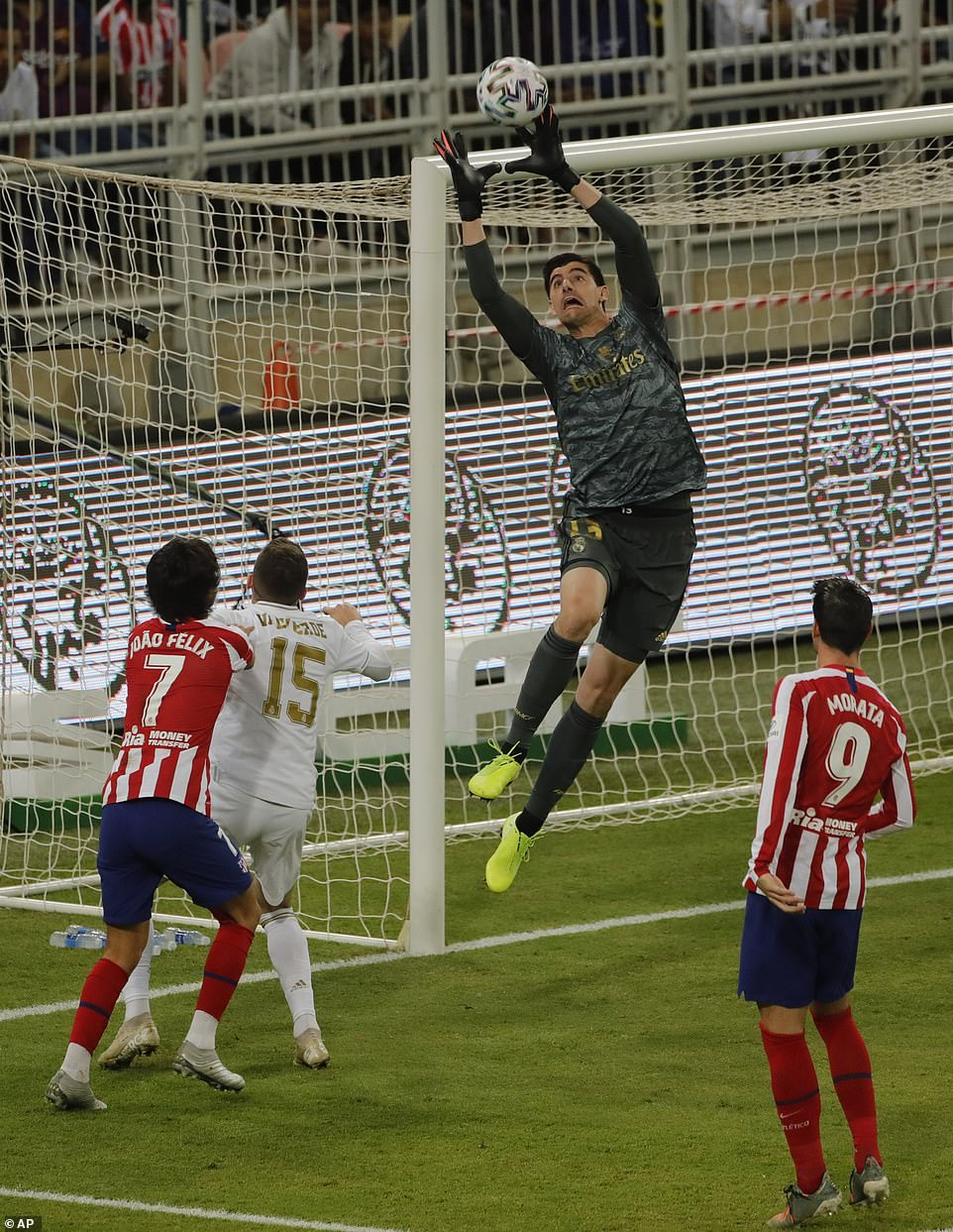 Real Madrid goalkeeper Thibaut Courtois goes up to catch the ball as he arrives towards his net from an Atletico Madrid shot