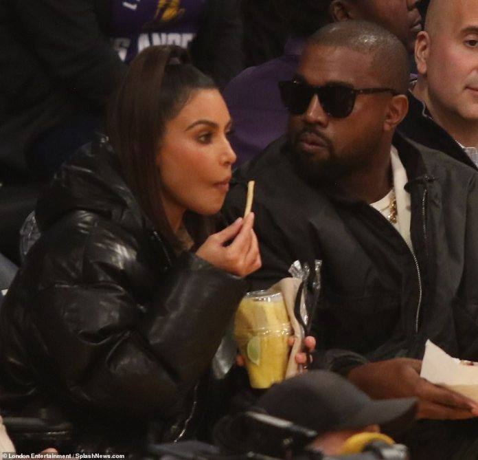 Caught in the moment: Kim couldn't tear her eyes away from the sport as she enjoyed a snack