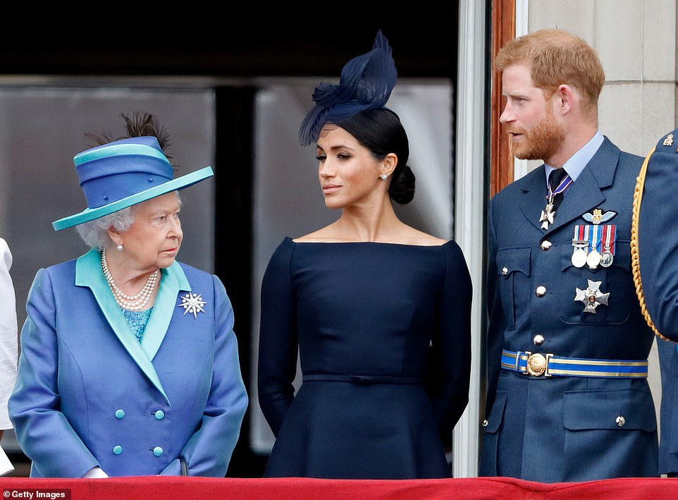 Queen Elizabeth II, Meghan, Duchess of Sussex and Prince Harry, the Duke of Sussex watch an air parade to celebrate the centenary of the Royal Air Force from the balcony of Buckingham Palace on 10 July 2018