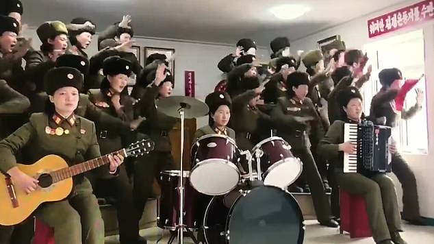 Performance: A troupe of North Korean women in military uniform dances for Kim Jong-un while some of the performers play a guitar, drum kit and accordion