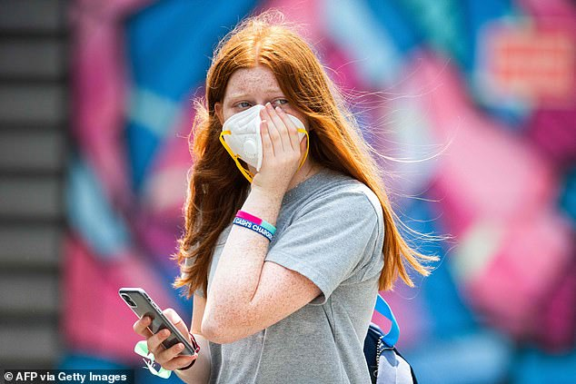 A woman clasps her breathing mask to her face during today's practice session of the Australian Open tennis tournament in Melbourne