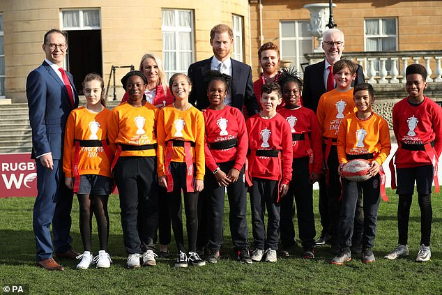 The Duke of Sussex and Jon Dutton (left), chief executive of the Rugby League World Cup 2021, pose with children who were playing rugby in the Buckingham Palace gardens in London today