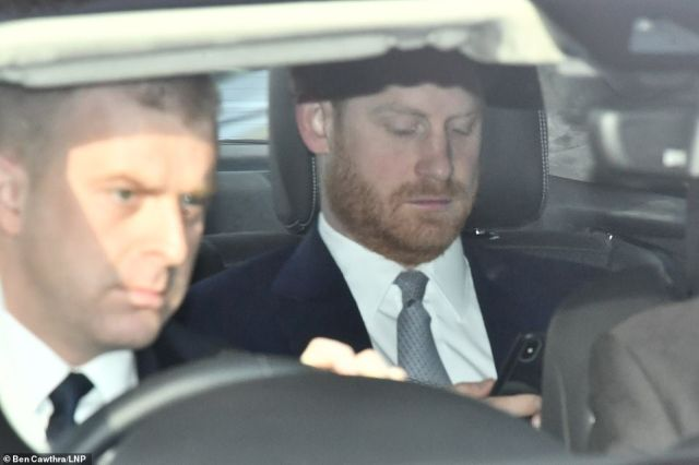 Prince Harry arrives at Buckingham Palace looking at his phone as he appears for the first time since quitting as a senior royal - and it could even be his swan song if no deal is struck with the Queen