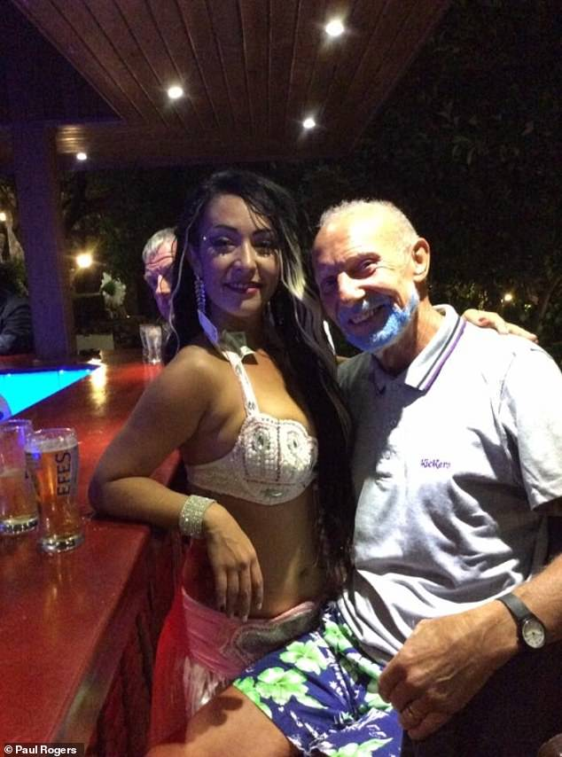 A guest standing with one of the hotel's performers at the bar. Two pints of beer are also visible