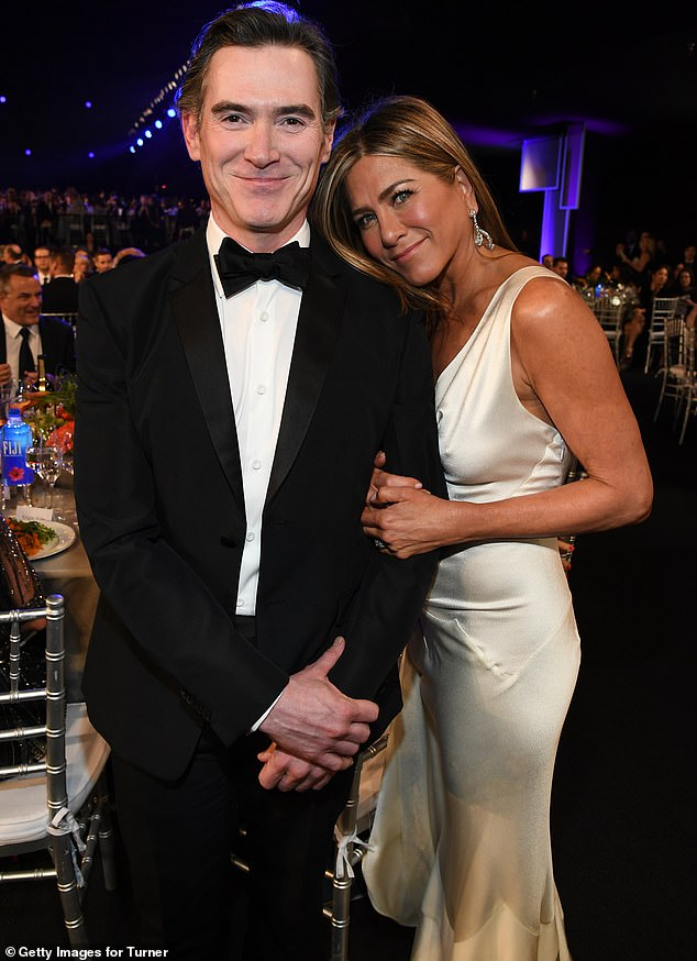Cozying up: Jennifer cuddled up to her The Morning Show co-star Billy Crudup as they prepared to settle down for the awards show