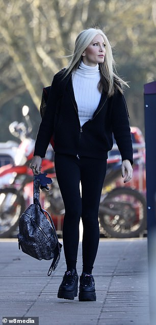 Happier: Earlier in the day she was seen looking sombre, but seemed more cheerful when snapped en route to training