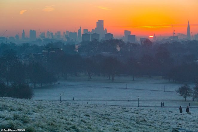 Frost covers the lawns as the sun rises behind the capital's skyline, as seen from Primrose Hill in North London today
