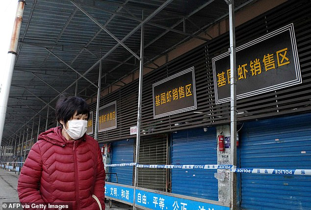 Authorities have pointed the blame on food markets in Wuhan. Pictured, a woman wears a mask while walking past the closed Huanan Wholesale Seafood Market