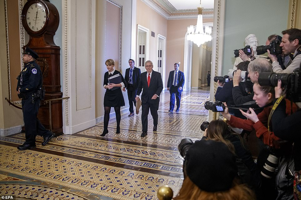 Ready for action: Mitch McConnell makes his way to the Senate chamber to speak - firing the starting gun on a drawn-out debate on how the trial will take place