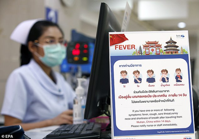 A Thai nurse works next to a campaign poster alerting patients of the coronavirus at a hospital in Bangkok, pictured today. Four cases have been confirmed in Thailand