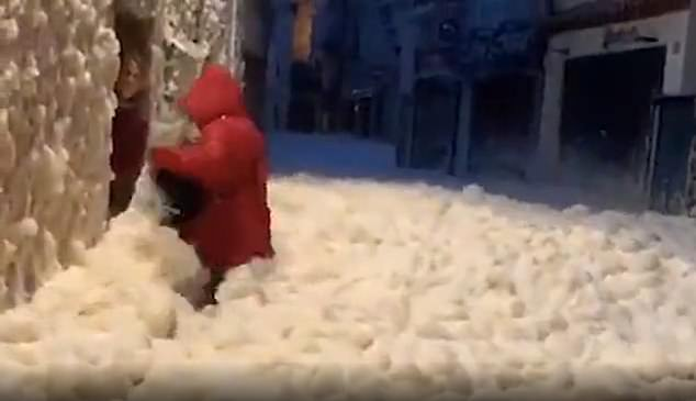 A woman tries to enter her home in the Costa Brava holiday resort of Tossa de Mar with sea foam filling the street up to her waist on Tuesday