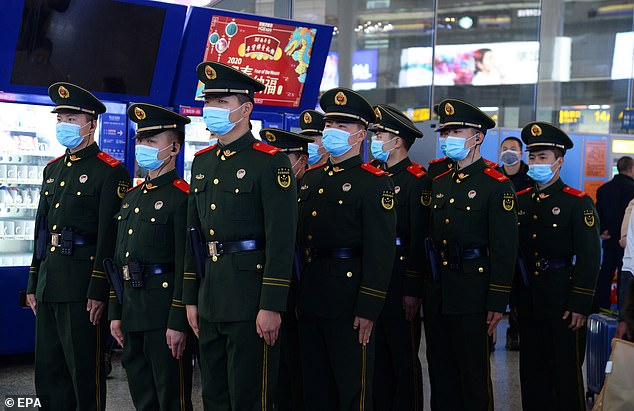 Chinese paramilitary police officers wearing masks patrol the Hongqiao Railway Station during peak spring festival travel in Shanghai today