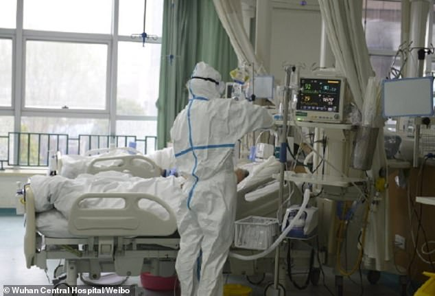 Another medic in hazmat suit is seen checking a medical device inside the hospital's intensive care units. At least 17 people have been killed by the virus since it emerged last month