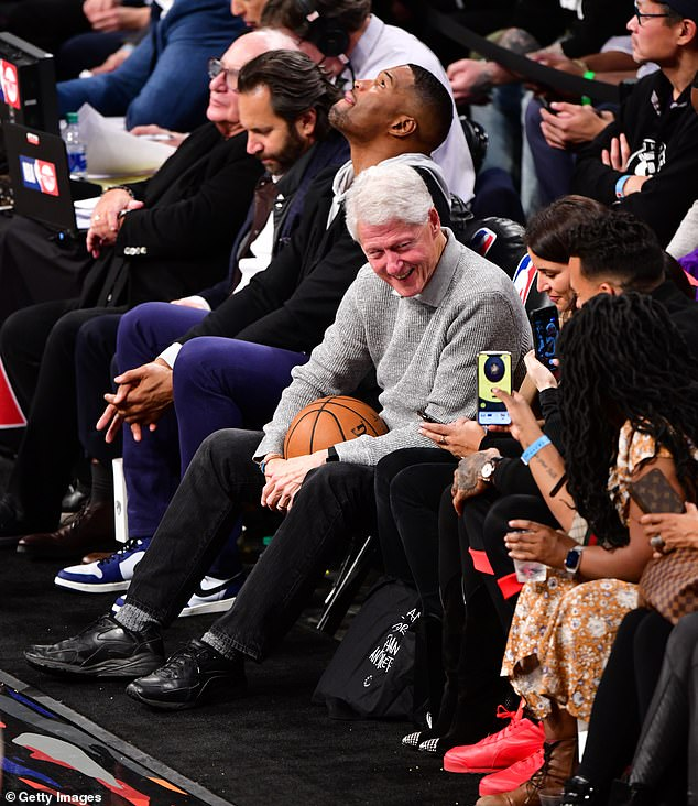 Mr Clinton can be seen sitting courtside, dressed in a casual grey sweater, black jeans and sports shoes clutching a basketball as he chats and laughs with those around him