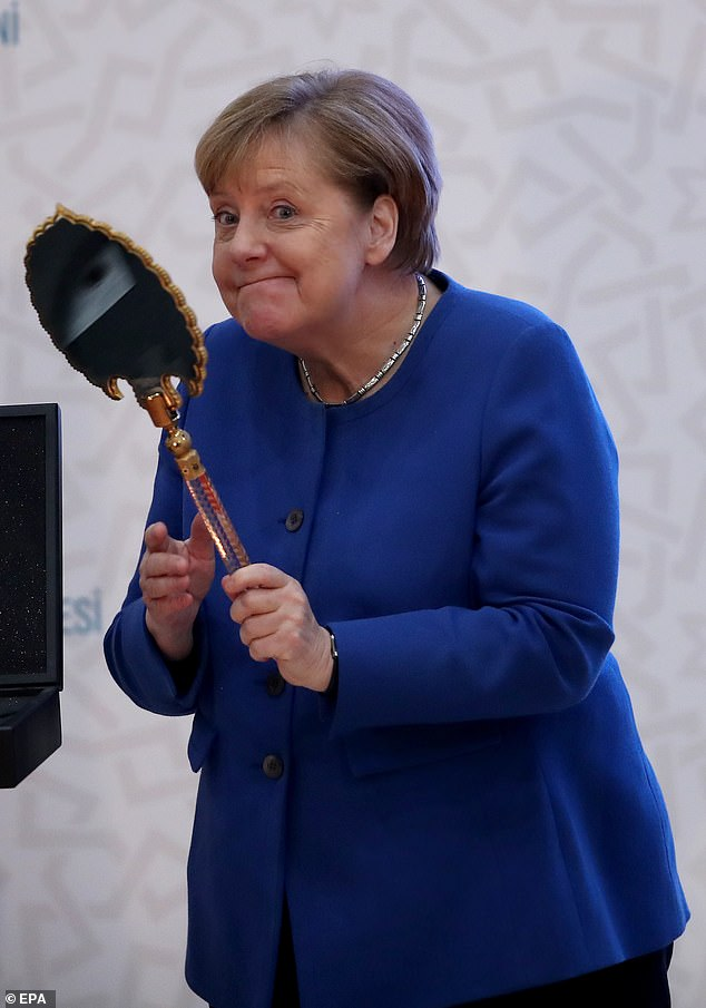 Merkel is presented with a mirror from Erdogan on Friday