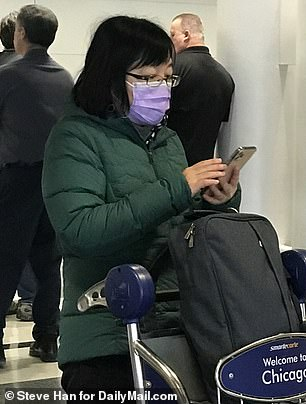 The CDC also issues its highest warning to level 3, which urges Americans to 'avoid unessential travel.' Pictured: Travelers with masks at O'Hare Airport on Thursday