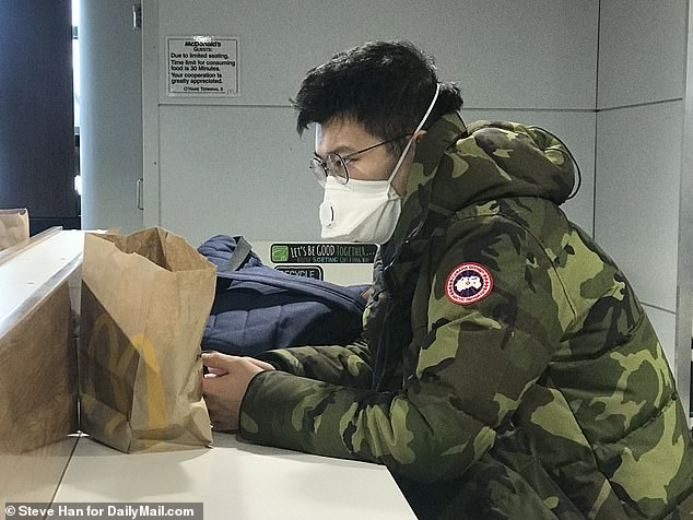 The US Department of State has issued its highest travel warning for Wuhan, advising Americans to not travel to the region. Pictured: A man wearing a mask at O'Hare Airport