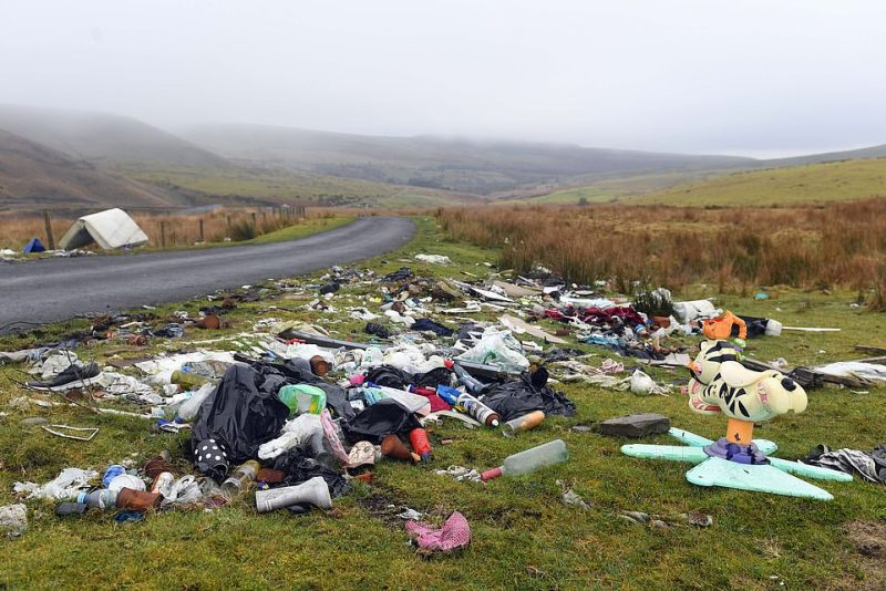 Wasteland in Merthyr Tidfil: A rubbish-strewn roadside in the area featuring plastic toys, rusting cans and a mattress