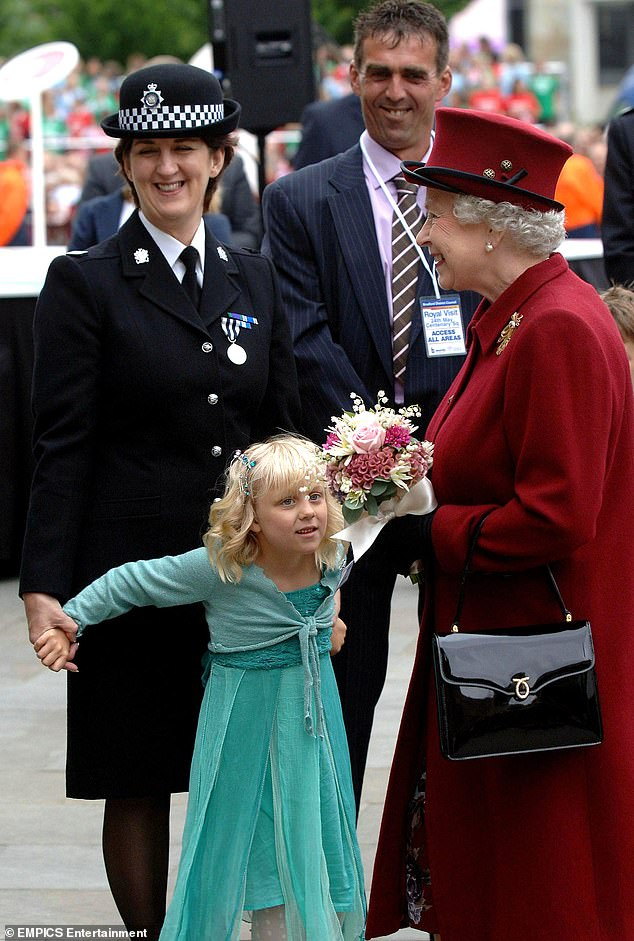 Queen Elizabeth II is presented with flowers by Lydia Beshenivsky, the daughter of murdered WPC Sharon Beshenivsky, during her visit to Bradford on May 25, 2007