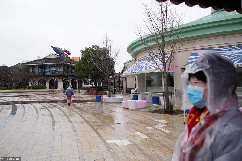 A member of staff wearing a mask is seen outside the Shanghai Disney Resort, that is closed today during the Chinese Lunar New Year holiday following the outbreak of a new coronavirus, in Shanghai