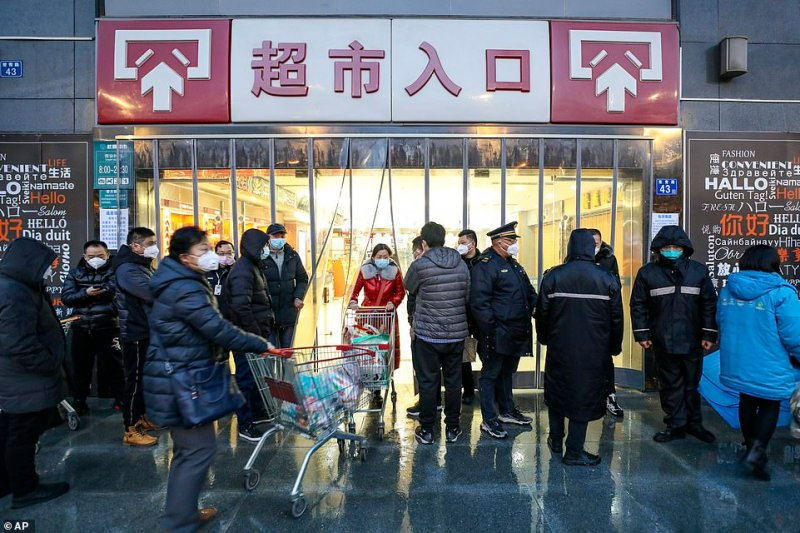 Shoppers wearing face masks exit a supermarket in Wuhan in central China's Hubei province today.The virus-hit Chinese city of Wuhan, already on lockdown, banned most vehicle use downtown and Hong Kong said it would close schools for two weeks as authorities scrambled to stop the spread of an illness that is known to have infected more than 1,200 people and killed 56, according to officials