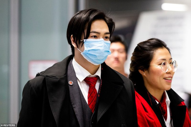 Travelers are seen above wearing masks at the arrival hall at Pearson airport in Toronto on Saturday