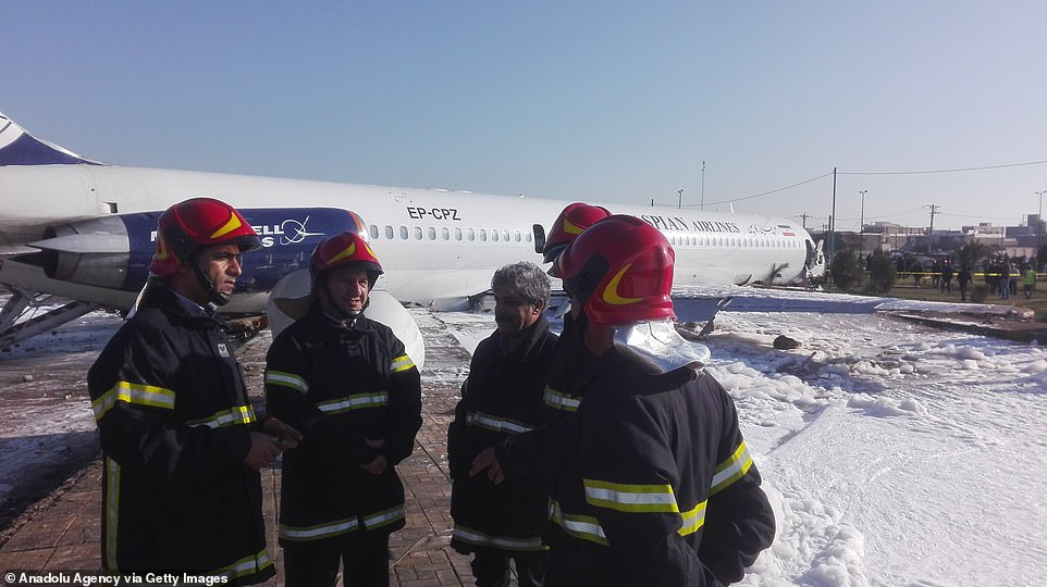 Fire crews douse the crashed aircraft with flame-retardant foam to stop any spilled fuel from catching fire after the Caspian Airlines plane skidded off the runway inMahshahr