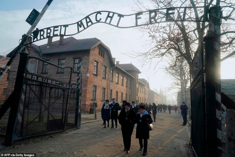 """Holocaust survivors walk below the gate with its inscription """"Work sets you free"""" after a wreath laying at the death wall at the memorial site of the former German Nazi death camp Auschwitz"""