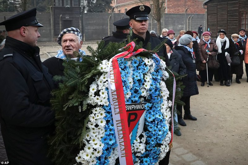 A survivor talks to one of the officers at the site as the ceremony gets underway on January 27, 2020