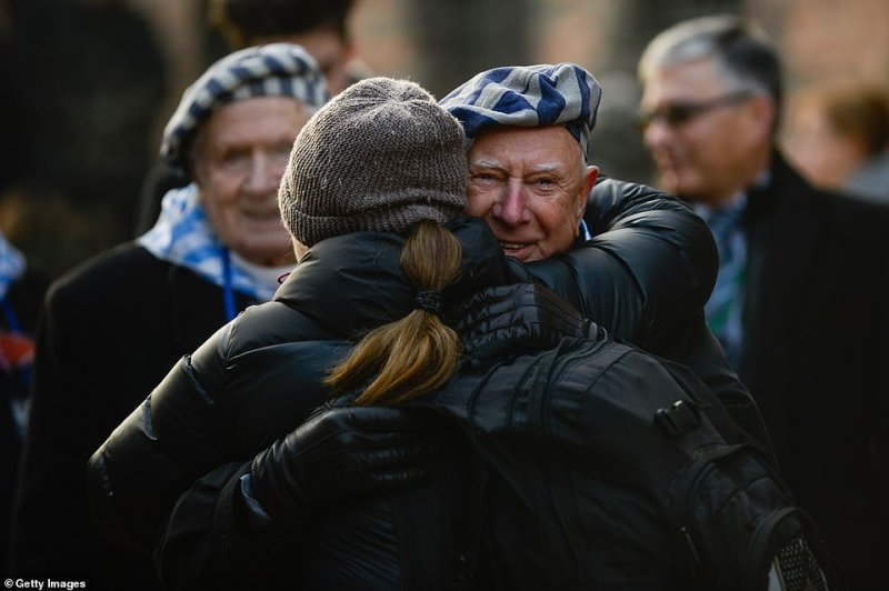 A survivor of the Auschwitz concentration camp hugs a woman after laying wreaths in honor of victims who were killed or died while imprisoned inside its walls