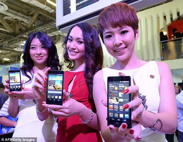 Many Tory MPs are furious at the prospect of the Chinese firm being allowed access and expressed their anger during an Urgent Question in the Commons yesterday. Huawei promoters are pictured with one of the Chinese telecoms company's phones