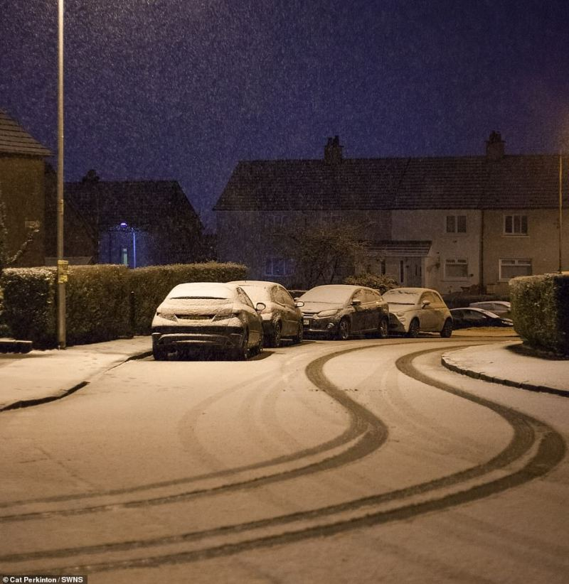 Tyre marks are seen in the snow in North Lanarkshire as many trudge through the white stuff to get to work and school today