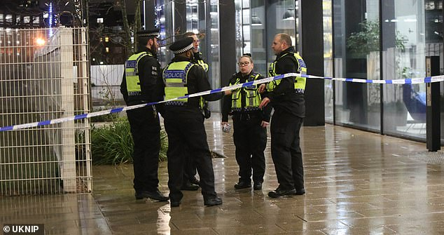 Police officers stood next to a cordon last night put in place near East Croydon railway station