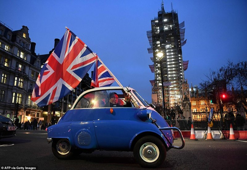 A man waves Union flags from a small car as he drives past Brexit supporters gathering in Parliament Square, near the Houses of Parliament in central London