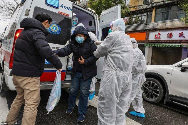 Pracownicy medyczni w odzieży ochronnej pomagają podejrzanemu pacjentowi z koronawirusem wydostać się z karetki w Wuhan