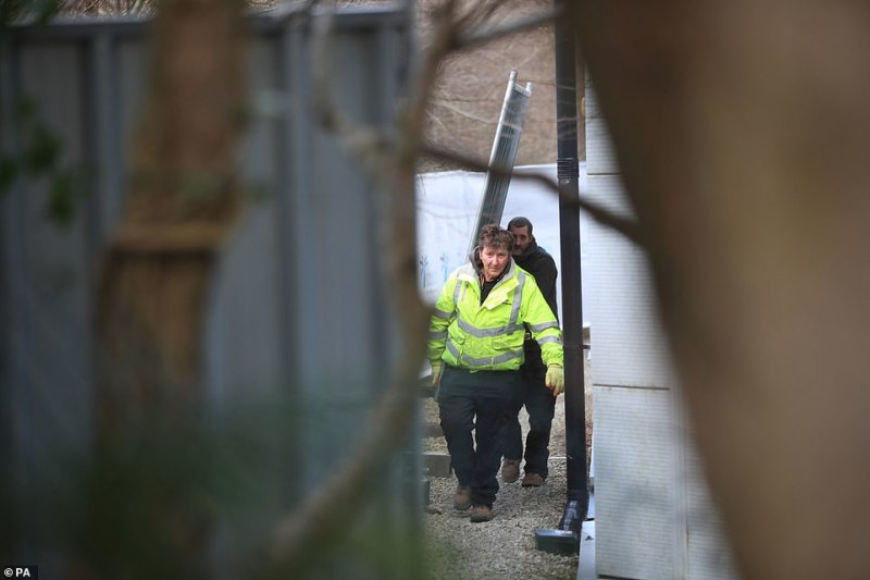 Workmen move a fencing panel at Arrowe Park Hospital in Merseyside, outside the block where British nationals from the coronavirus-hit city of Wuhan in China are being quarantined