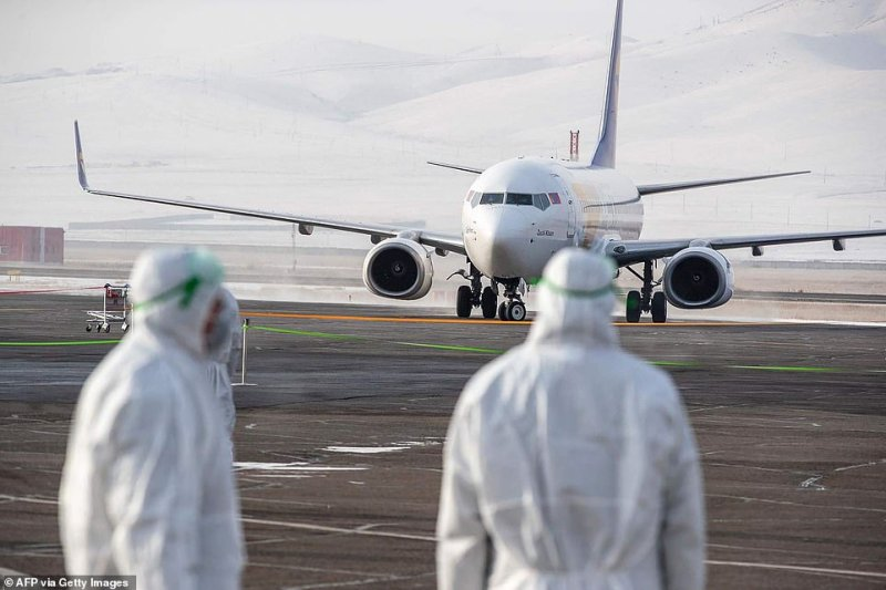 Staff members, wearing protective suits, watch as a plane carrying 32 Mongolian citizens for their evacuation from the Chinese city of Wuhan arrives in Ulaanbaatar, the capital of Mongolia today
