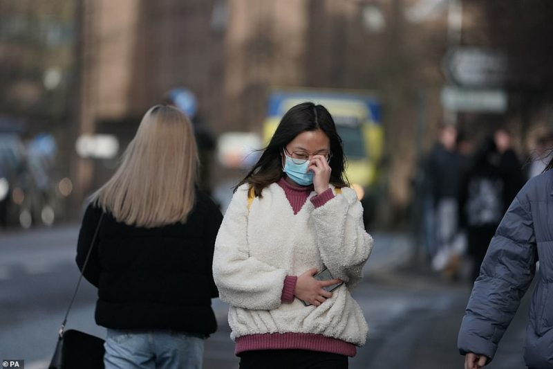 A woman wears a mask in Newcastle upon Tyne, near where two patients who have tested positive for coronavirus this week