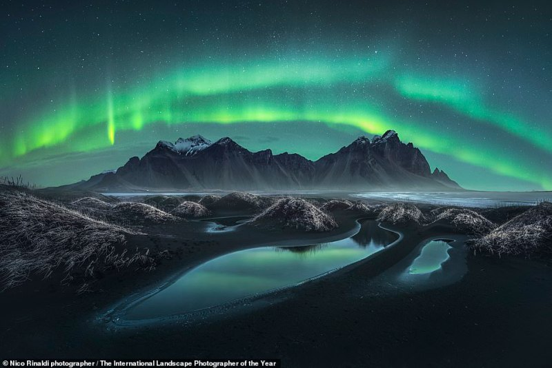In this shot, theVestrahorn in Iceland is captured beneath the alien-green glow of the Northern Lights. It was snapped by Italian photographerNico Rinaldi