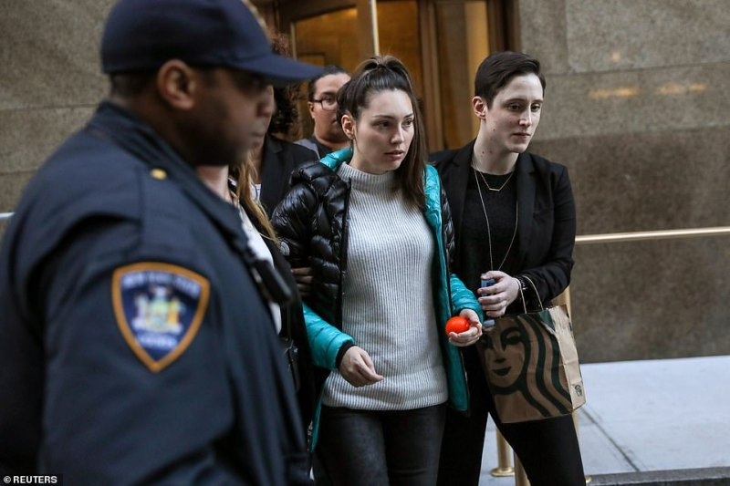 Mann pictured above in the white ribbed sweater holding onto what appears to be a stress ball as she was ushered into a car following an exhaustive cross-examination on Monday