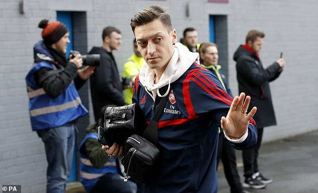 Arsenal's Mesut Ozil waves as he arrives for the Premier League match at Turf Moor against Burnley on Sunday