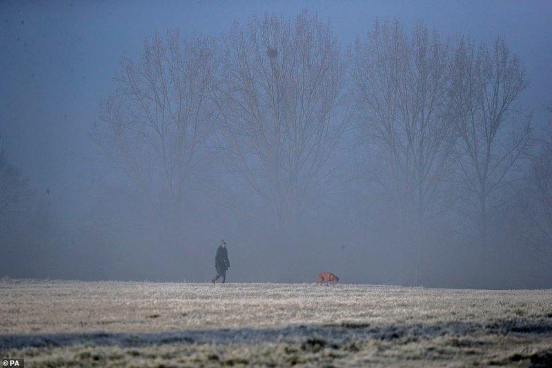 A dog walker makes their way through fog near Windsor in Berkshire this morning