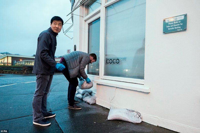 The cafe's owners hope that sandbags will keep out the rain being swept in by the high winds