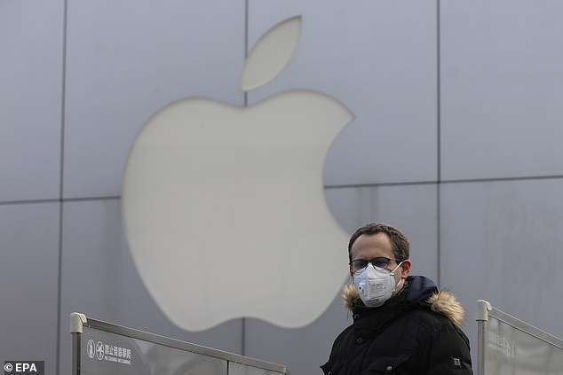 The virus has forced businesses with Chinese operations to close factories. Those affected include iPhone maker Apple. Pictured:A man wears mask as he walks past a closed Apple store at Sanlitun in Beijing, China