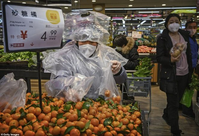 A Chinese wearing protective paraphernalia to ward off coronavirus shops for groceries in Beijing on Tuesday