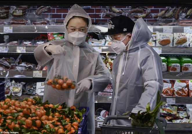 A Chinese couple wear plastic coats and protective masks as they shop for groceries at a supermarket in Beijing on Tuesday. China on Wednesday reported 97 more coronavirus deaths, pushing the total dead on the mainland to 1,113