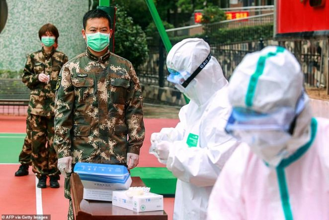 Chinese paramilitary police officers waiting to be tested for coronavirus as they return from holidays in Shenzhen in China's southern Guangdong province on Tuesday. The number of fatalities from China's new coronavirus epidemic jumped to 1,113