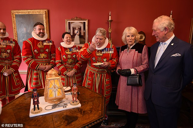 Pictured: Camilla and Charles cut a cake shaped like a lantern as they chat with Yeoman Warders