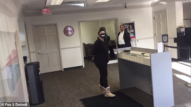 In a video taken by her boyfriend, Ulmen is seen waiting calmly for police to arrive after a teller pressed the panic button when she refused to remove the mask and the bank is locked down