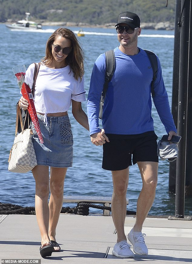 Loved-up:In the pictures, the pair look smitten as they kiss and hold hands after a day on Sydney Harbour